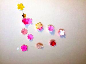 母の居室の壁に咲いた、折り紙で作った桜の花。床ずれ防止で2時間おきに体位交換をしていたが、壁側を向いたときに白一色では切ないだろうと、同じホームにいる高齢者とスタッフたちが共同で作ってくれた。この後、徐々に壁を覆うように数が増え、最後は満開だった=鳥居りんこさん写す