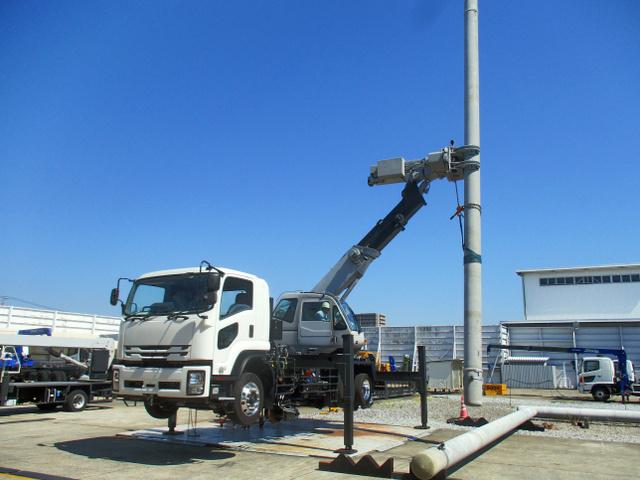 電柱をアームでつかんで交換する新車両(JR西日本提供)