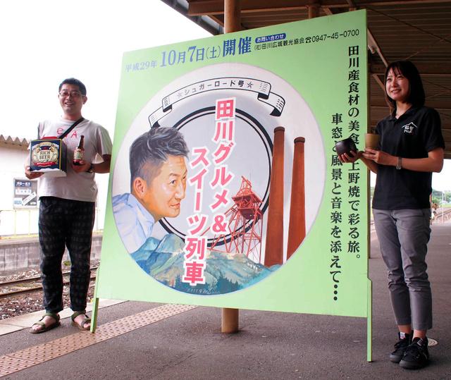 田川グルメ&スイーツ列車をPRするスタッフとレトロ調の看板=福智町の平成筑豊鉄道