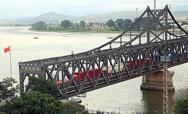 中国遼寧省丹東と対岸の北朝鮮新義州を結ぶ「中朝友誼橋」を通るトラック。この橋は中朝貿易の主要ルートだ=8月10日、平賀拓哉撮影