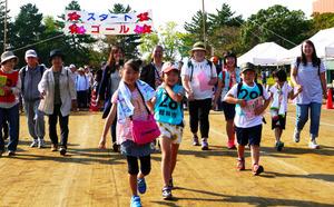 仲間や家族らと歩く参加者たち=館林市つつじ町の城沼陸上競技場