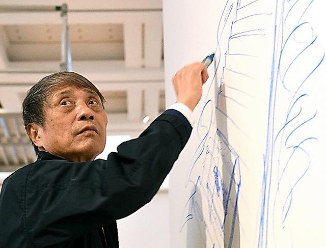 展覧会場の壁にドローイングを描く安藤忠雄=山本和生撮影