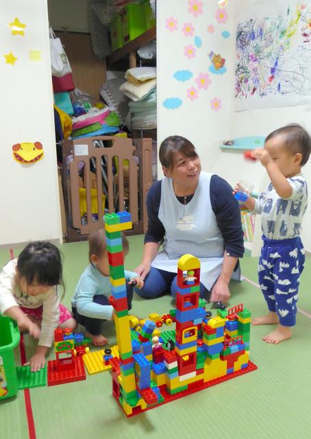 親の迎えを待つ子どもらと遊ぶ保育士の早川桂子さん=東京都武蔵野市