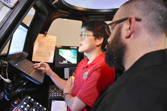 宇宙ステーションを模したシミュレーターで、ロボットアームを使った訓練をする金井宣茂宇宙飛行士(左)=12日、米ヒューストン、香取啓介撮影