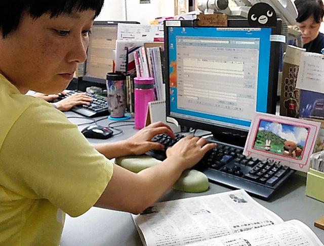 雑誌に目を通し、検索で記事が引っかかりやすくなるよう多くのキーワードを入力する小林恭子さん=東京都世田谷区の大宅壮一文庫