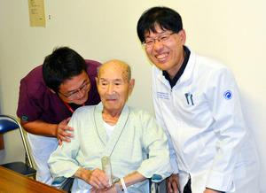 森下清文医師(右)らと会見に臨み、笑顔を見せる男性=函館市立函館病院
