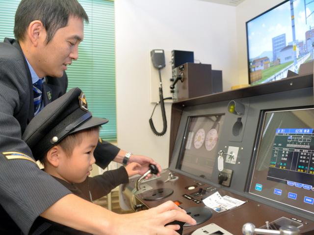 JRの運転士に教わりながら電車の運転シミュレーターを体験する子ども=豊岡市大手町
