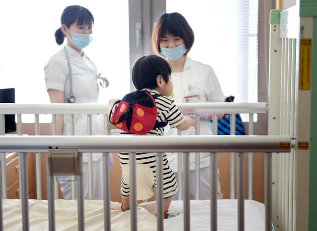 肺移植を受けた女の子。退院の朝、看護師に声をかけられて立ち上がった=岡山市の岡山大、遠藤真梨撮影