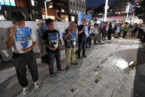 ツイッター社に抗議し、路上に問題視するツイートを敷き詰めて踏みつける参加者=9月8日夕、東京都中央区、角野貴之撮影