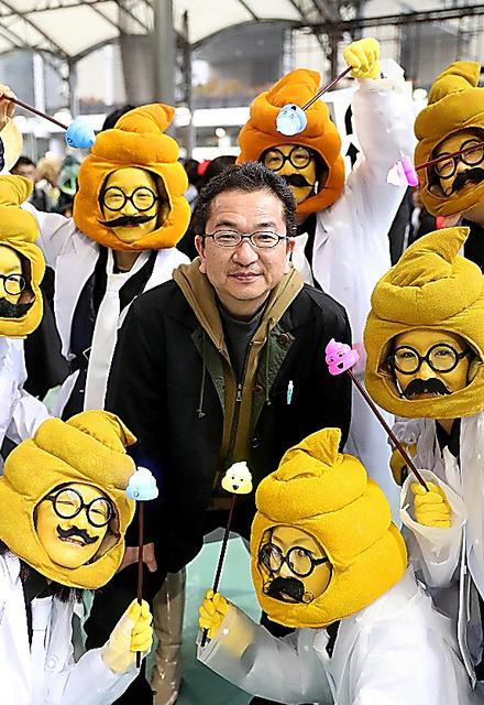 土岐一利さん=29日、「うんこ漢字ドリル」がモチーフの仮装者に囲まれて、柴田悠貴撮影