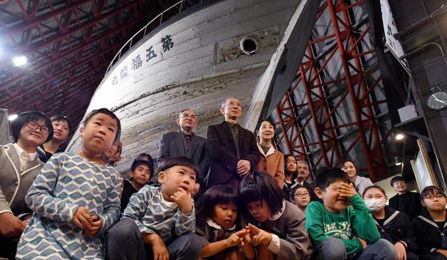 第五福竜丸の建造70年を記念する企画展のオープニングセレモニーに参加した人たち。(中央後方の左から)元船員の大石又七さん、男鹿和雄さん、吉永小百合さん=5日午後、東京都江東区、角野貴之撮影