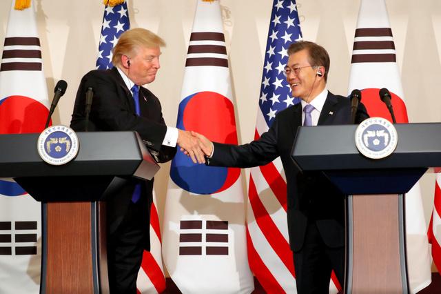 ソウルで7日、共同記者会見で握手する米国のトランプ大統領(左)と韓国の文在寅大統領=ロイター