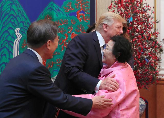 7日、韓国大統領府で開かれた夕食会で元慰安婦の李容洙(イヨンス)さん(右)を抱擁するトランプ米大統領。文在寅(ムンジェイン)大統領(左)が見守った=東亜日報提供