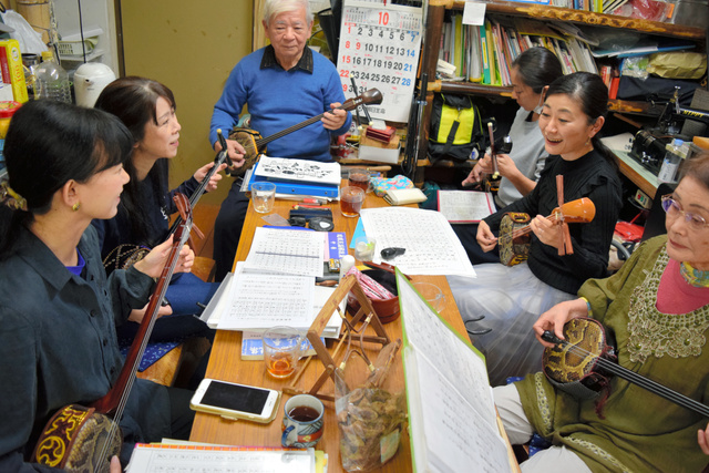 三線屋「とぅるるんてん」で三線を指導する宮城富士男さん(奥)と生徒たち=東京都杉並区の「沖縄タウン」