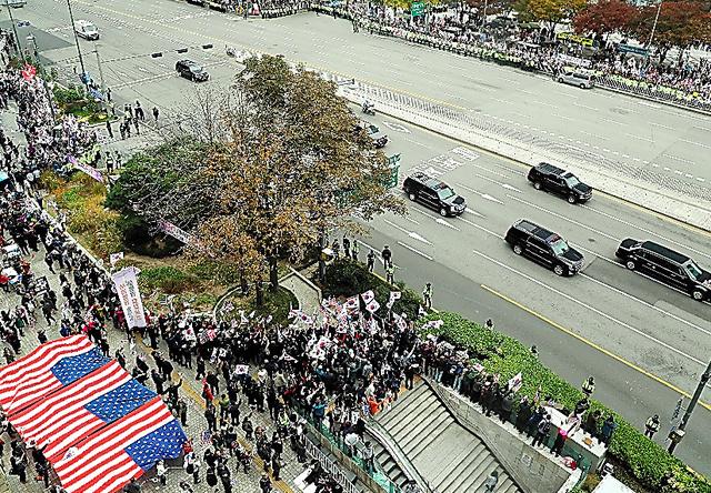 7日午後、歓迎と反対の市民の声が交錯するなか、韓国大統領府に向かうトランプ米大統領らの車列=東亜日報提供