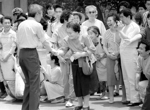 避難所を訪れ、手を差し出す住民に応える天皇陛下=1991年7月10日、島原市、朝日新聞社撮影