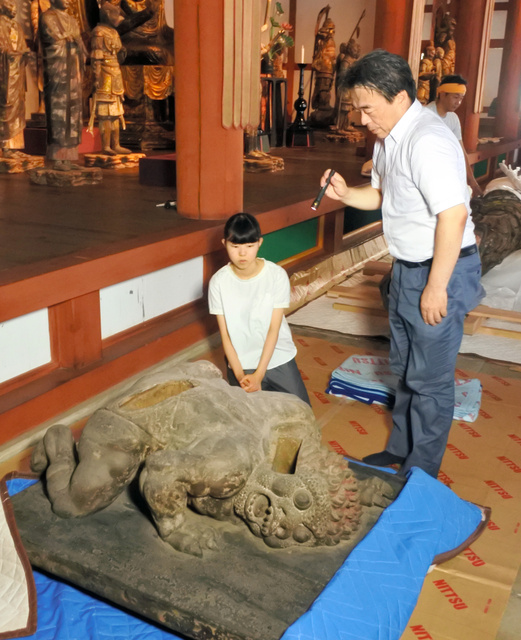 運慶の父、康慶が造った四天王像の邪鬼について、東京国立博物館の浅見龍介・企画課長から説明を聞く飯島可琳さん=7月26日午前、奈良市の興福寺、小滝ちひろ撮影