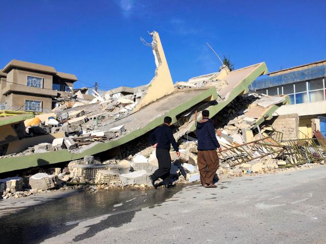 イラク北部スレイマニア県で13日、地震で崩壊した建物のそばを通る人々=ロイター