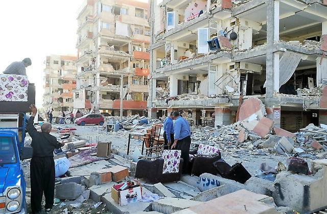 イラン西部ケルマンシャー州のサレポレザハブの中心部で、地震で崩れた建物に集まる人たち=13日、杉崎慎弥撮影