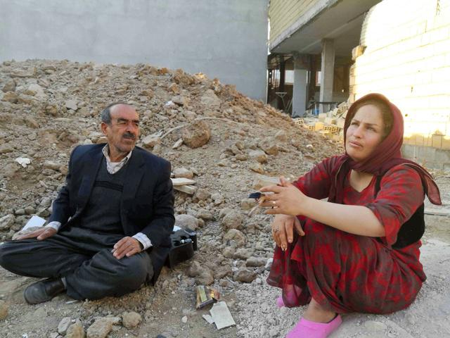 イラン西部サレポレザハブで13日、損壊した家屋の片付けに疲れ果てて、がれきの上に座り込む人たち=杉崎慎弥撮影