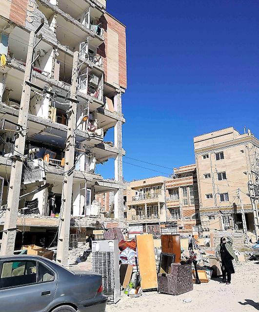 地震で壁が崩れ落ちた「愛情住宅」(左)。隣接する一般住宅(右奥)には目立つ損傷がなかった=14日、イラン西部サレポレザハブ、杉崎慎弥撮影