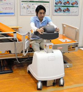 歩行器がリモコン操作でベッドのわきまで自動走行する。スイッチを操作すると、ベッドと持ち手が適切な高さまで上がる=北九州市小倉北区、井石栄司撮影