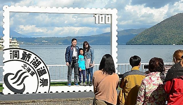 洞爺湖畔の写真撮影スポットでは、外国人観光客が列をなしていた=北海道洞爺湖町
