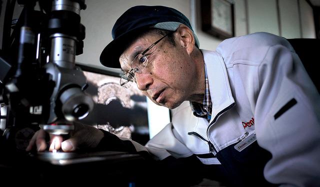顕微鏡で部品をチェックする。「人によって筆圧も書く時の角度も違うので、誰もが心地よいと感じる書き味を目指して設計してます」=埼玉県吉川市、村上健撮影