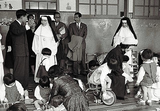 鹿児島市の児童養護施設で子どもに声をかける美智子さまと、立って職員と話す皇太子明仁さま=1962年5月8日、朝日新聞社撮影