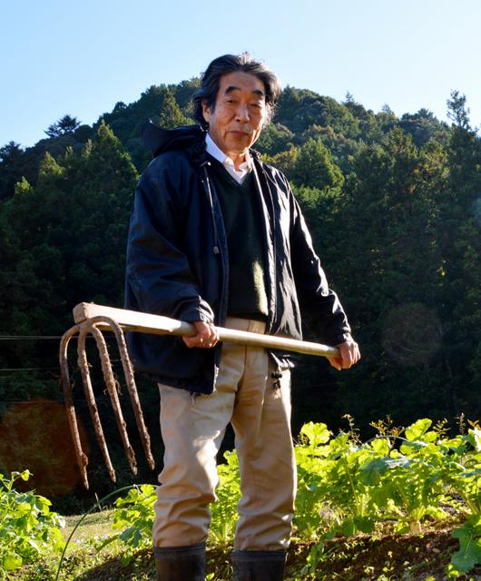 畑でくわを手にする秋山さん=三重県大台町