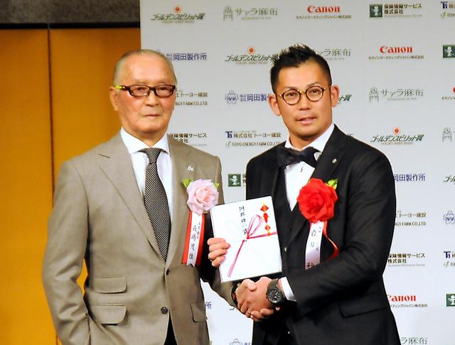 長嶋茂雄氏(左)から目録を受け取った阪神の岩田