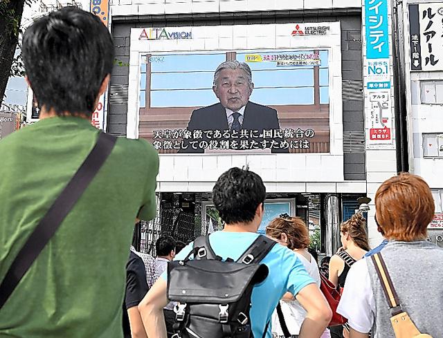 天皇陛下のビデオメッセージを放送する大画面を見る人々=2016年8月8日、東京・新宿、朝日新聞社撮影