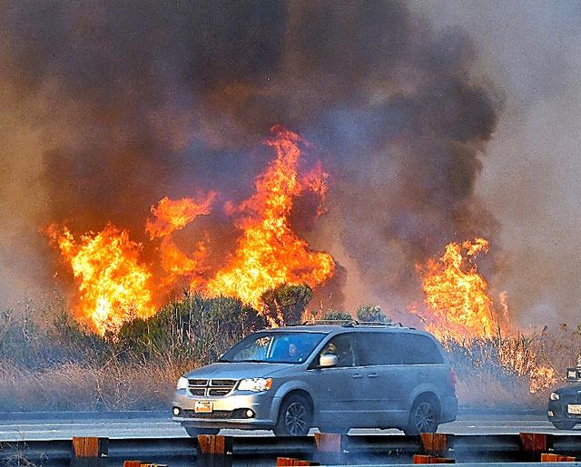 米カリフォルニア州ベンチュラで7日、国道脇で広がる原野火災=AFP時事