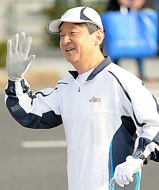 沿道の人に手を振りながらジョギングをする皇太子さま=15年2月、皇居外周