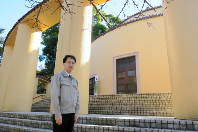 丘の上に立つ旧多摩聖蹟記念館と芳野貴典さん=東京都多摩市