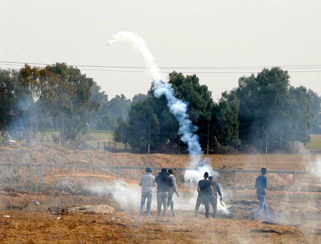 パレスチナ自治区ガザのイスラエルとの境界近くで10日、イスラエル軍が撃ち込んだ催涙ガス弾を投げ返すパレスチナ人の若者たち=杉本康弘撮影