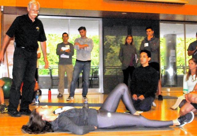 カールアップを指導するマックギル名誉教授(左)。腹筋に力を入れ、首を固定したうえで胸部を屈曲させる