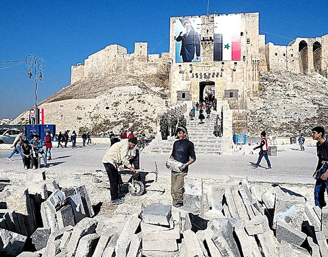 アサド政権軍と反体制派の激戦が続いたアレッポ城前では、砲弾の着弾で傷んだ石畳を張り替える作業が進められていた。城門にはアサド大統領の巨大な写真が掲げられていた=12日