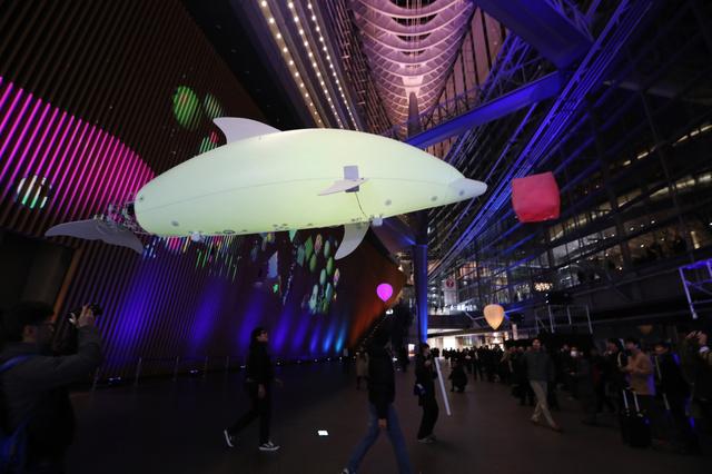 東京国際フォーラムのガラス棟を泳ぐイルカ型のバルーン=19日午後6時39分、東京都千代田区、関田航撮影