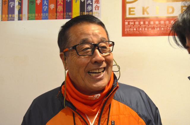往路で4位に入った後、笑顔でインタビューを受ける拓大の岡田監督
