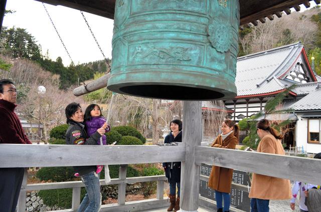 今年から昼間に変わった「除夜の鐘」をつく家族連れ=大槌町の吉祥寺