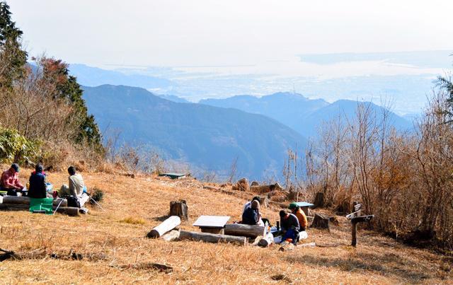 竜爪山の文殊岳山頂でくつろぐ登山者たち。遠景は駿河湾の清水港付近。右上は三保の松原