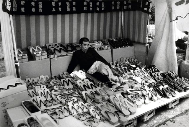 げたを売る男性。この姿勢で足にげたを載せて磨く。かっこよく撮ってほしいとポーズ=1989年5月、浅草寺境内