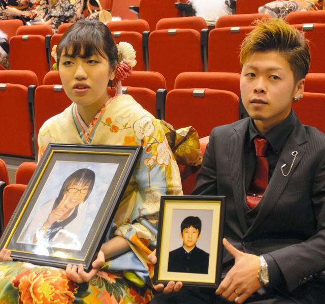 川崎千香さんの遺影を持つ田中理子さん(左)と佐々木悠真さんの遺影を持つ吉田隼人さん=大槌町城山公園体育館