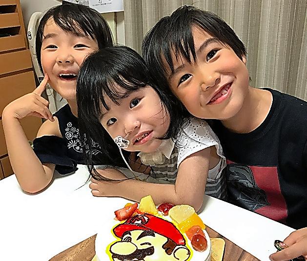 琳果ちゃん(中央)はお兄ちゃん(右)とお姉ちゃんに囲まれ、すくすく成長している=6月、家族提供