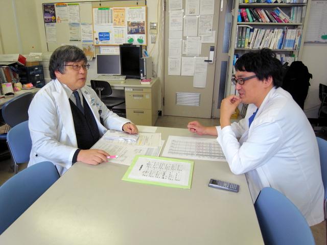 中国で学び、日本で資格を取った横山央医師(右)。埼玉医科大の研究室で中元秀友教授と談笑する