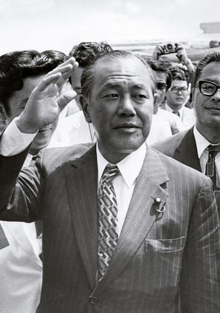 右手を挙げポーズをとる田中角栄首相