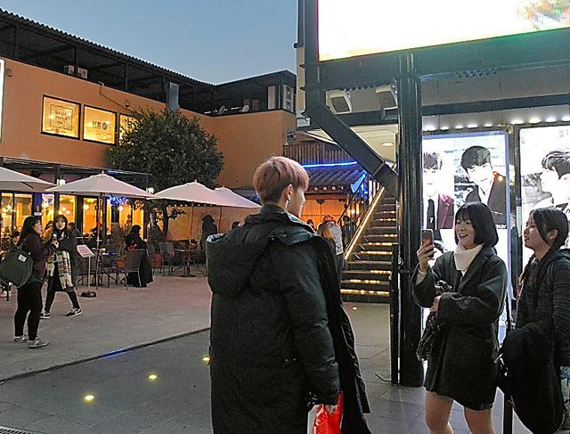 「大使館」の駐車場跡には今、Kポップのライブハウスが立つ。若手アーティストと触れ合うファンの姿も=東京都新宿区