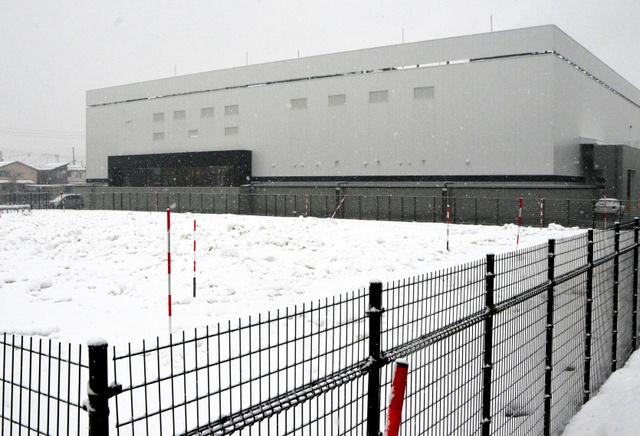 長岡市内に開所したデータセンター。2月末までに手前の敷地に最大4千立方メートルの雪を積む。木片チップを敷き詰め、シートをかぶせることで夏季も雪が溶けないという=22日、長岡市内