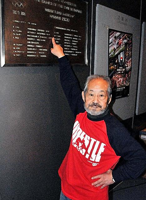 渡辺長武。東京五輪レスリングの優勝者の名を刻んだ銅板の前で=駒沢体育館